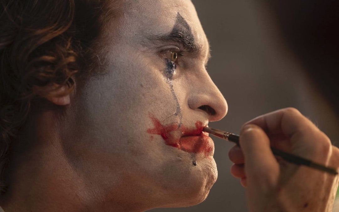 Joaquin Phoenix layers paint on as the Joker (Credit: Warner Bros.)