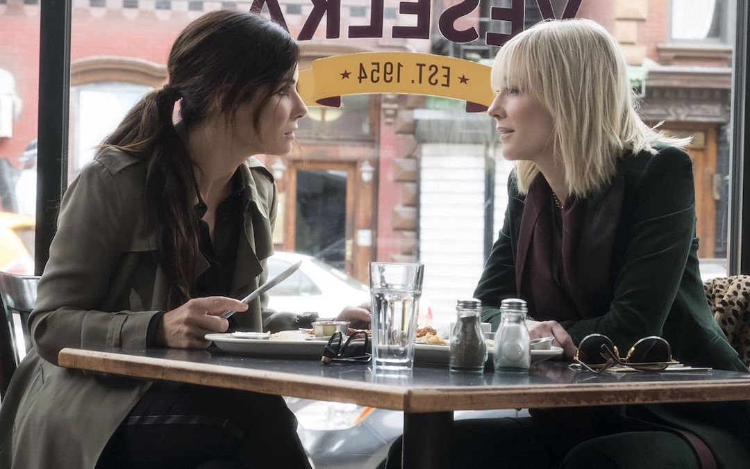 Sandra Bullock and Cate Blanchett with food they never eat and water glasses that have never been filled in 'Ocean's Eight' (Courtesy: Warner Bros.)