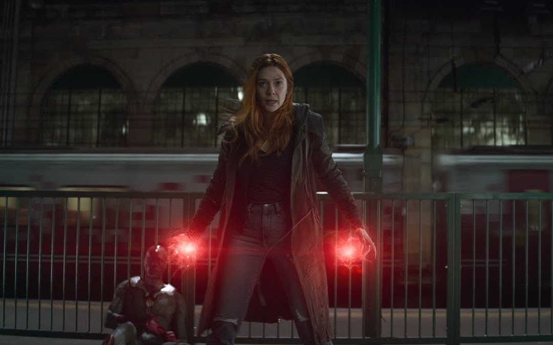 Scarlet Witch stands with her arms outstretched emanating red balls of energy from her palms, ready to defend a wounded Vision.