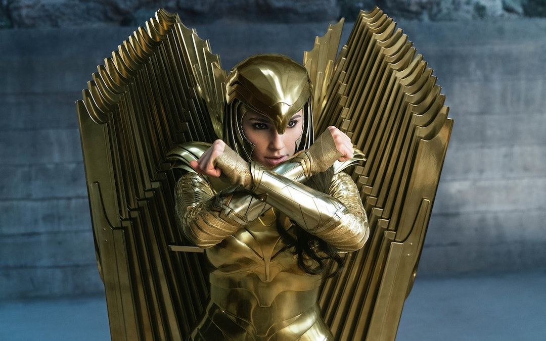 A dark-haired woman stands in a defensive stance in golden, winged armor